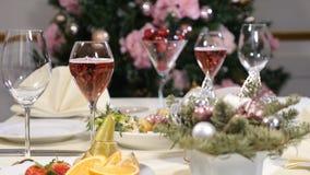 Conceito do restaurante Tabela da festa do ano novo e do Feliz Natal bolhas do champanhe no vidro Prato de fruto cortado, queijo vídeos de arquivo