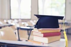 Conceito do símbolo da educação do estudo O tampão da graduação é livros de texto superiores na sala de aula foto de stock royalty free
