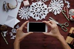 Conceito do `s do ano novo As mãos do ` s das mulheres guardam um smartphone, flocos de neve cortados do papel, presentes da foto imagens de stock