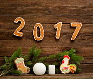 Conceito do `s do ano novo Pão-de-espécie, ramo spruce e o número 2017 no fundo de madeira Imagens de Stock