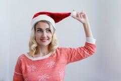 Conceito do ` s do Natal e do ano novo Mulher loura nova bonita em um sorriso do tampão do ` s do ano novo Contra uma parede bran fotografia de stock