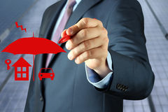 Conceito do seguro do desenho do homem de negócios por uma pena vermelha Fotos de Stock