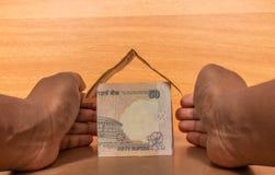 Conceito do seguro patrimonial, mãos que protegem a casa feita com moeda de papel indiana foto de stock