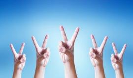 Conceito do sucesso: Uma mão que faz o gesto do número dois no fundo azul foto de stock royalty free