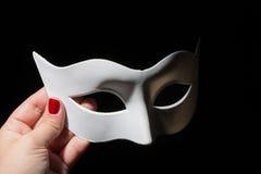 Conceito do teatro ou do carnaval Mão fêmea que guarda a máscara plástica branca no fundo preto foto de stock
