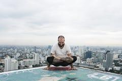 Conceito do telhado da ioga da prática do homem fotografia de stock