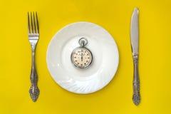 Conceito do tempo do almoço Pulso de disparo com faca e forquilha Fotos de Stock