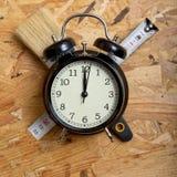 Conceito do tempo de DIY Ferramentas que cercam um despertador preto foto de stock royalty free
