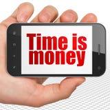 Conceito do tempo: Mão que guarda Smartphone com Tempo é dinheiro sobre exposição Imagens de Stock Royalty Free