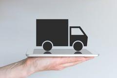Conceito do transporte/modelo comercial digitais disruptivos da logística Mão que guarda a tabuleta ou o grande telefone esperto Fotos de Stock