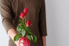 Conceito do Valentim, homem que guarda rosas vermelhas no fundo branco Foto de Stock Royalty Free