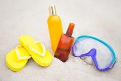 Conceito do verão - falhanços de aleta, garrafas da loção para bronzear e miliampère de mergulho Fotografia de Stock Royalty Free