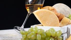 Conceito do vinho e do queijo Conceito da arte do alimento Amantes do queijo Variedade de queijo colocada na placa de madeira com filme
