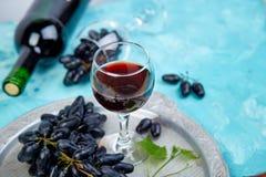 Conceito do vinho tinto com garrafa, vidro e uvas fotos de stock royalty free
