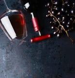 Conceito do vinho tinto O vidro com vinho tinto, garrafa e a uva vermelha aglomera-se no fundo rústico preto, vista superior fotografia de stock
