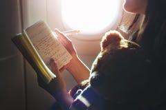 Conceito do voo do plano do livro de leitura da mulher imagens de stock