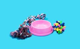 Conceito dos acessórios do animal de estimação Corda, bacias e brinquedo de borracha no azul fotografia de stock