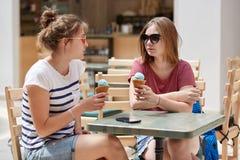 Conceito dos amigos, da recreação e do verão Dois adolescentes fêmeas bonitos comem o gelado delicioso frio, falam um com o otro, fotos de stock