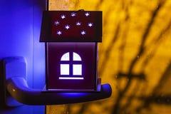Conceito dos bens imobiliários com uma casa de madeira do brinquedo pequeno no punho de janela A ideia do conceito de bens imobil imagem de stock