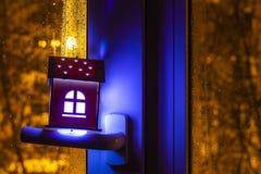 Conceito dos bens imobiliários com uma casa de madeira do brinquedo pequeno no punho de janela A ideia do conceito de bens imobil fotografia de stock