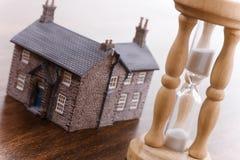 Conceito dos bens imobiliários do Hourglass e da casa foto de stock royalty free