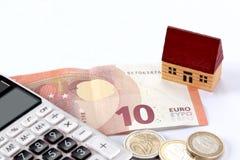 Conceito dos bens imobiliários e da hipoteca: casa do brinquedo, euro- conta, moedas e uma calculadora no fundo branco com espaço foto de stock royalty free
