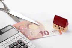 Conceito dos bens imobiliários e da hipoteca: casa do brinquedo, euro- conta, tesouras e uma calculadora no fundo branco com espa fotos de stock royalty free