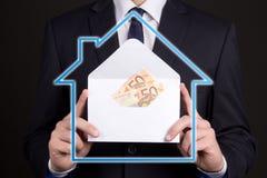 Conceito dos bens imobiliários e da hipoteca - envelope com dinheiro no busine imagens de stock