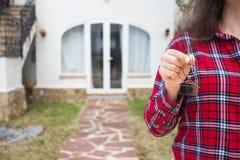 Conceito dos bens imobiliários e da propriedade - feche acima da mulher as chaves da casa que da terra arrendada na casa deram fo imagens de stock royalty free
