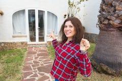 Conceito dos bens imobiliários e da propriedade Posse feliz Jovem mulher atrativa que guarda chaves ao estar exterior contra fotos de stock