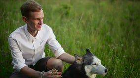 Conceito dos cães de puxar trenós Siberian do homem e do cão Homem novo asiático com seu cão no prado video estoque