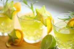 Conceito dos cocktail - três cocktail do verde amarelo que estão na madeira, decorada com laranja, carambola, cal e alecrins Apro Fotos de Stock Royalty Free