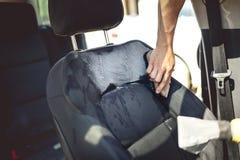 Conceito dos cuidados com o carro - detalhe do banco do condutor usando ferramentas e líquidos de limpeza profissionais fotografia de stock royalty free