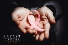 Conceito dos cuidados médicos - a criança entrega guardar a fita da conscientização do câncer Imagem de Stock