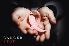 Conceito dos cuidados médicos - a criança entrega guardar a fita da conscientização do câncer Fotografia de Stock
