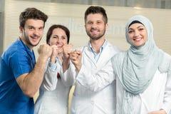 Conceito dos cuidados médicos e da medicina - doutor masculino atrativo na frente do grupo médico no hospital que mostra os poleg Fotos de Stock