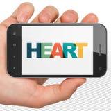 Conceito dos cuidados médicos: Mão que guarda Smartphone com coração na exposição Foto de Stock Royalty Free