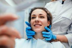 Conceito dos cuidados m?dicos e da medicina Paciente feliz da mulher que olha no espelho nos dentes, sentando-se na cadeira denta fotos de stock
