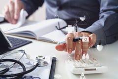 Conceito dos custos e das taxas dos cuidados médicos A mão do doutor esperto usou um Ca imagens de stock royalty free