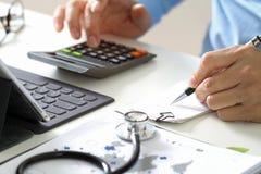 Conceito dos custos e das taxas dos cuidados médicos A mão do doutor esperto usou um Ca fotografia de stock royalty free