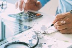 Conceito dos custos e das taxas dos cuidados médicos A mão do doutor esperto usou um Ca fotos de stock