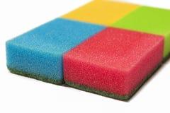 Conceito dos eletrodomésticos: Quatro esponjas coloridas da cozinha junto isola Fotos de Stock Royalty Free