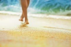 Conceito dos feriados das férias - silhueta dos pés sol-bronzeados da mulher shoeless que anda ao longo do litoral imagem de stock