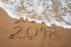 Conceito dos feriados O ano novo feliz 2018 substitui 2017 na praia do mar Fotografia de Stock Royalty Free