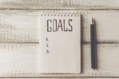 Conceito dos objetivos Caderno com lista dos objetivos na tabela de madeira motivation Imagem de Stock