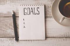 Conceito dos objetivos O caderno com objetivos alista, copo do chá na tabela de madeira motivation Foto de Stock