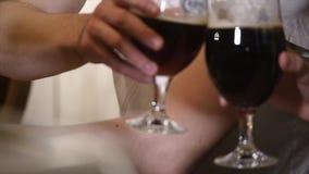 Conceito dos povos, do brinde, do lazer, da amizade e da celebração - amigos masculinos felizes que bebem vidros da cerveja e do  vídeos de arquivo