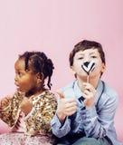 Conceito dos povos do estilo de vida: crianças diversas da nação que jogam junto, menino caucasiano com a menina africana que gua Imagens de Stock