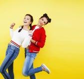 Conceito dos povos do estilo de vida: dois adolescentes consideravelmente novos da escola que têm o sorriso feliz do divertimento Imagens de Stock Royalty Free