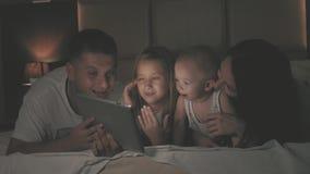 Conceito dos povos e de família - mãe feliz, pai, filha pequena e filho do bebê com o computador do PC da tabuleta na cama na noi filme